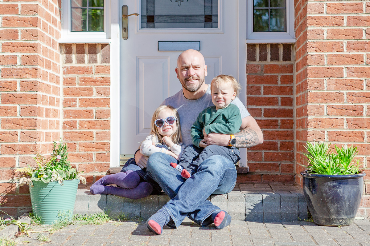 daddy sat on doorstep with daughter and son