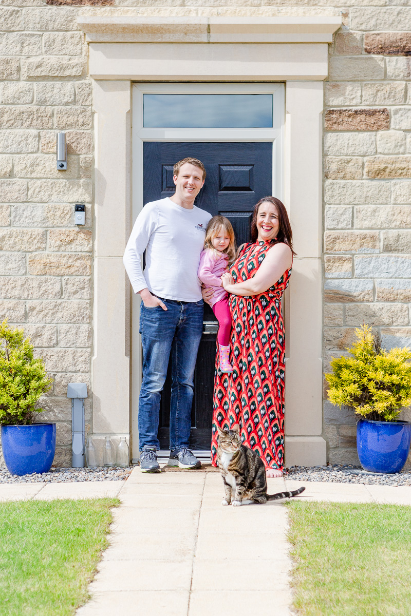 a mummy and daddy with daughter and cat on doorstep