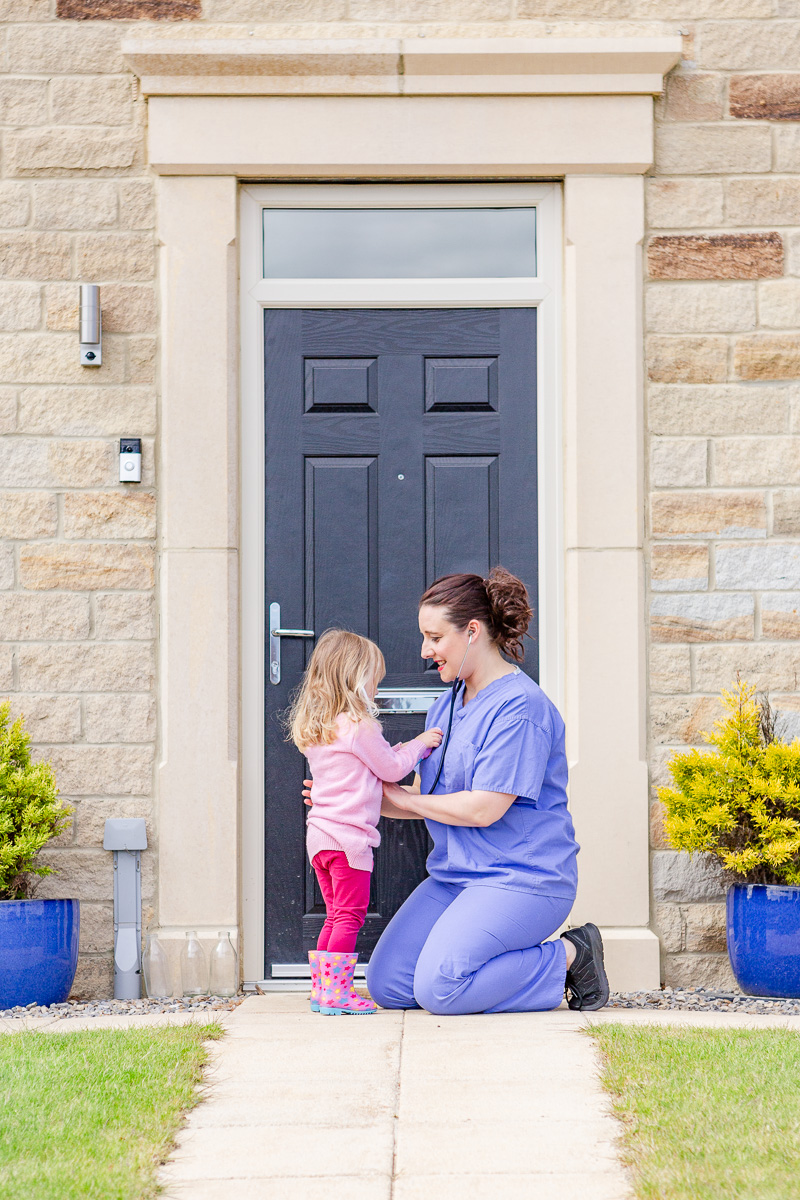 a mummy in NHS scrubs bending down listening to daughters heart on doorstep