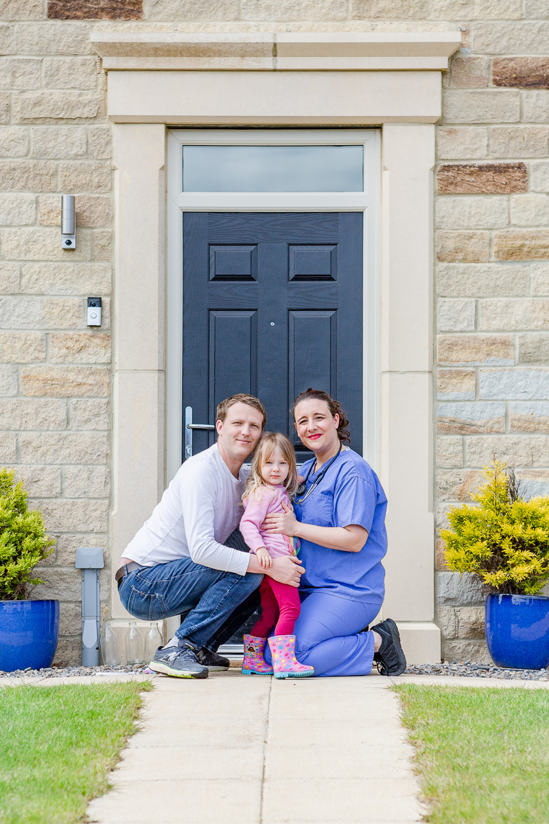 a mummy in scrubs with husband and daughter on doorstep