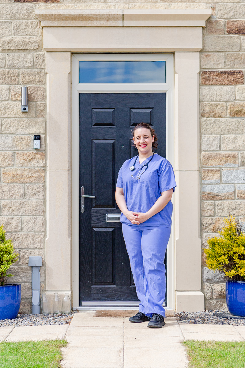 a lady doctor stood on doorstep in scrubs