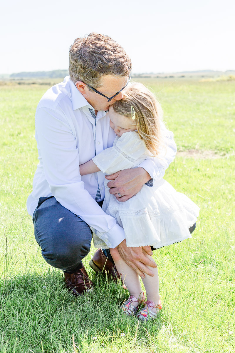 dad cuddling daughter in field