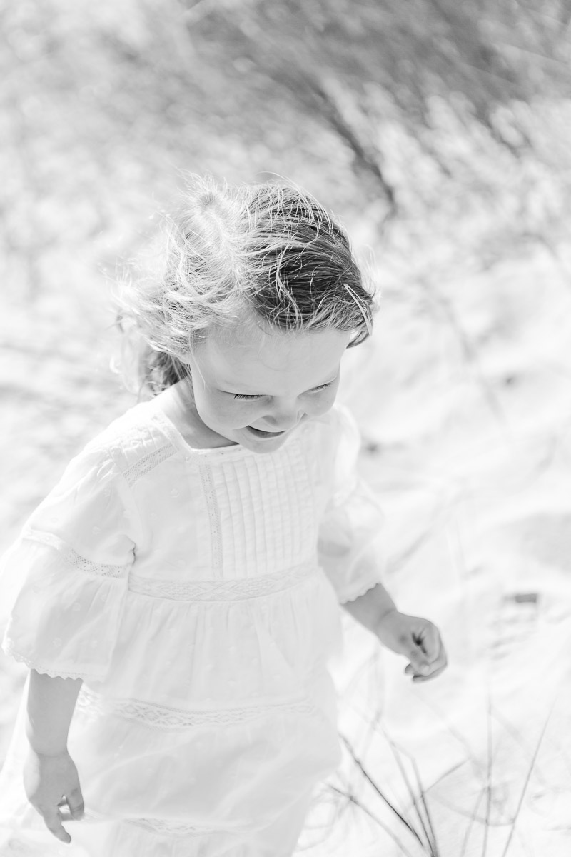black and white image of toddler walking in sand
