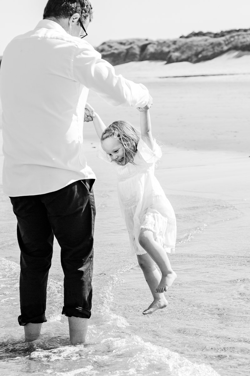 daddy and daughter playing in the sea black and white