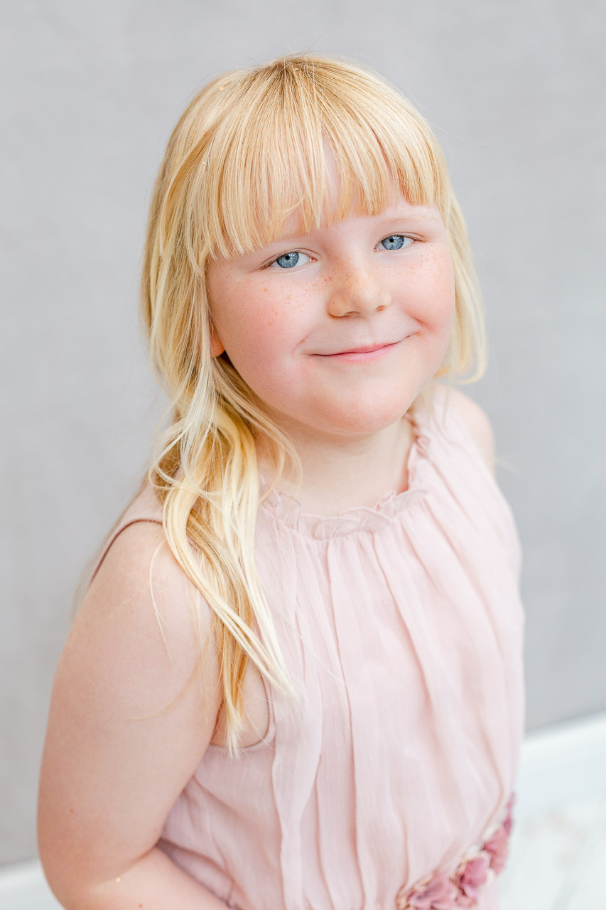 little girl smiling into camera in photography studio
