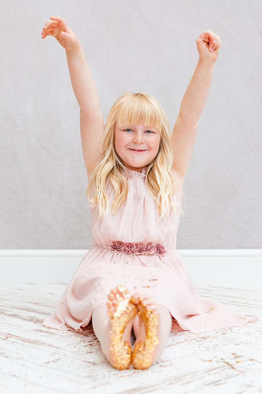 little girl sat on photography studio floor with feet covered in glitter and arms in the air