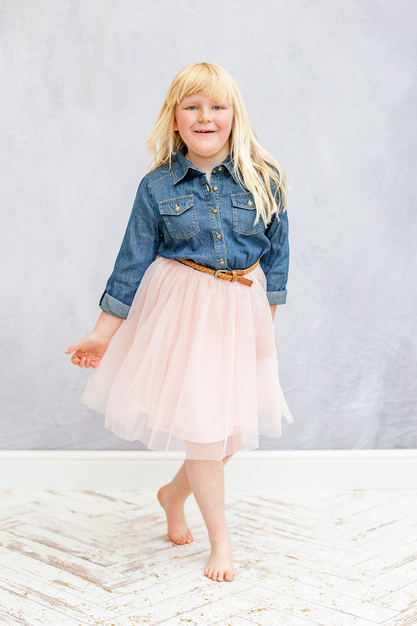 little girl dancing in studio wearing denim and tulle dress