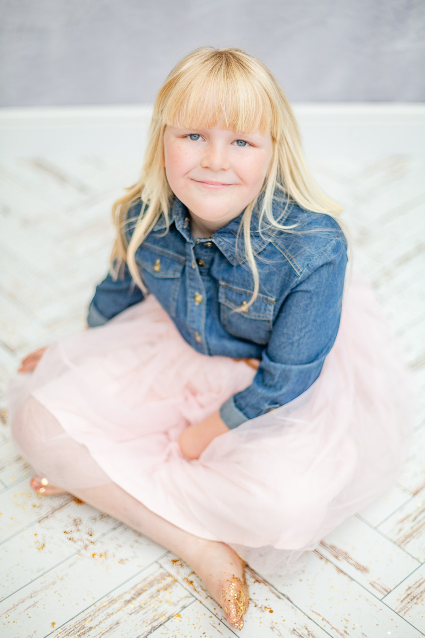 little girl sat smiling at camera with denim and tulle dress
