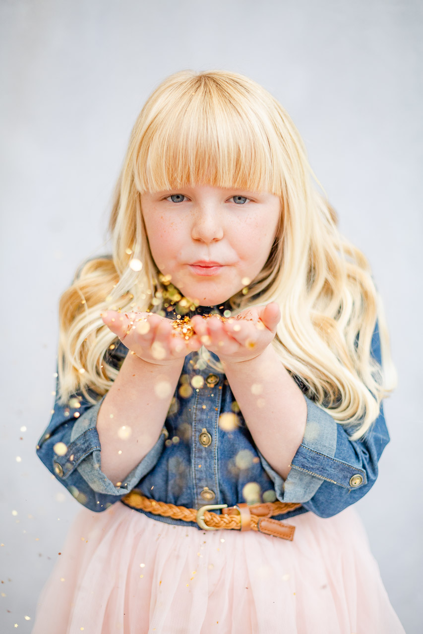 little girl blowing glitter at camera for glitter photo shoot
