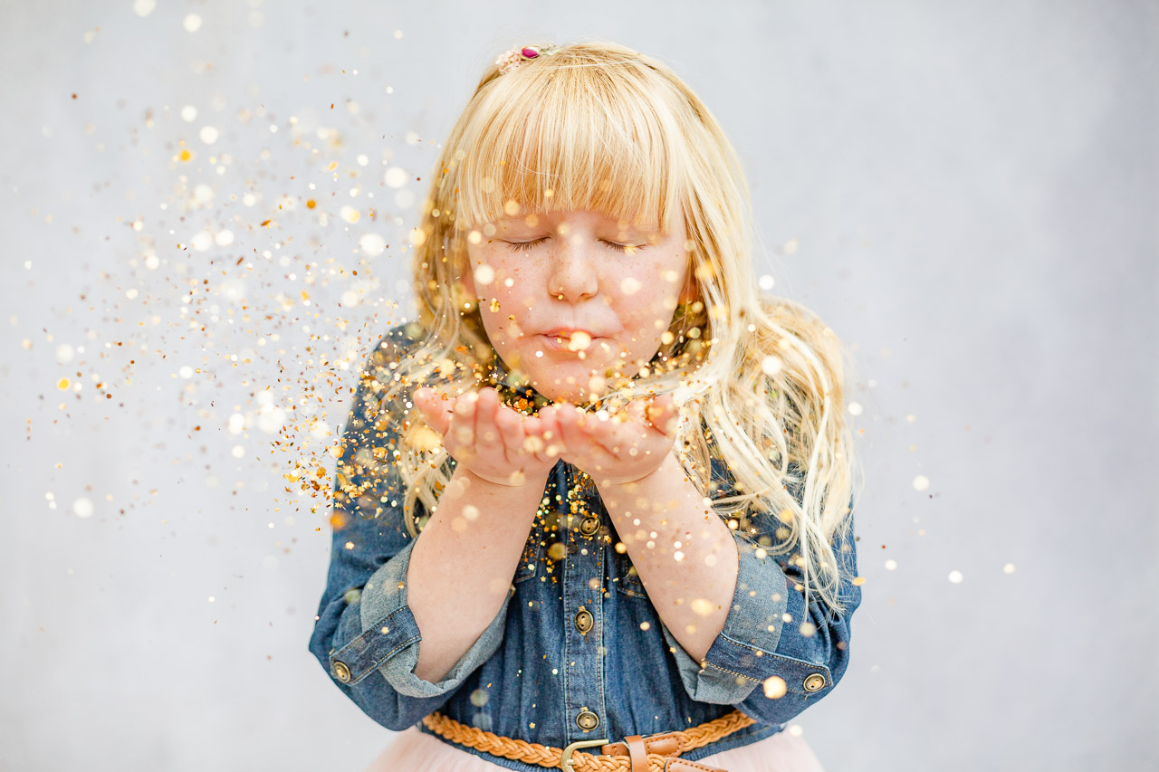 little girl blowing glitter in glitter photo shoot
