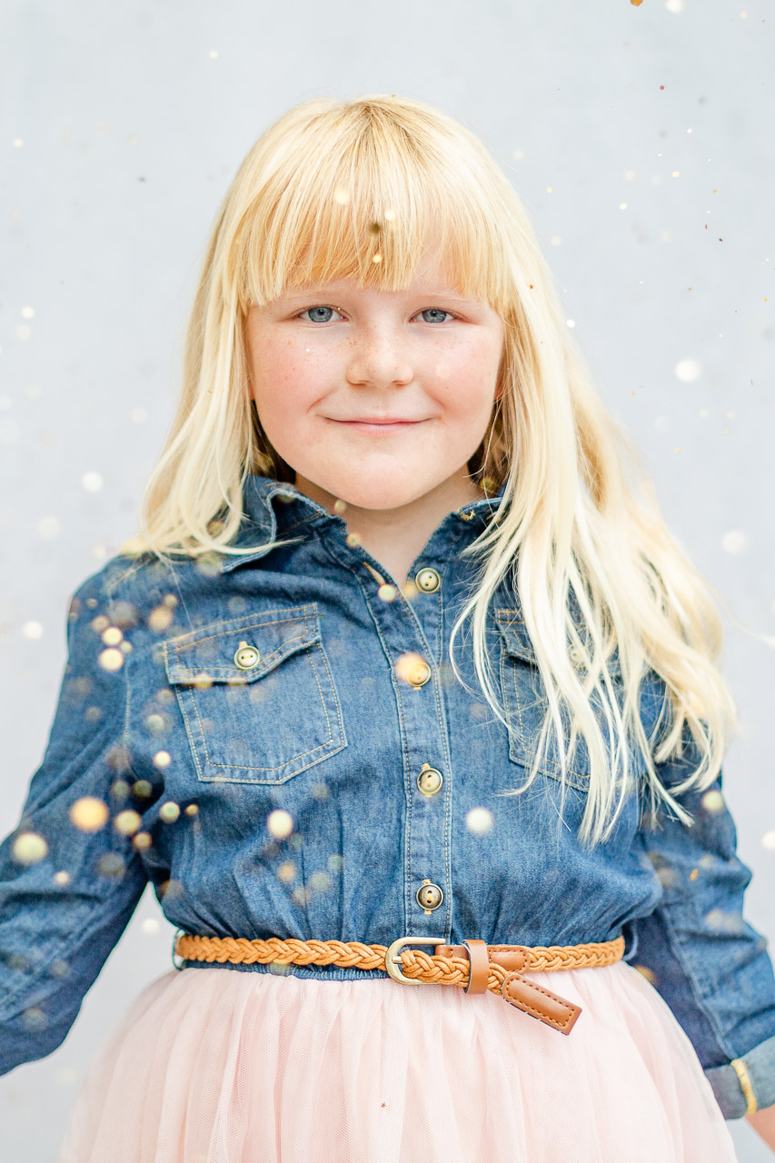 girl smiling into camera with glitter falling all around for glitter photo shoot