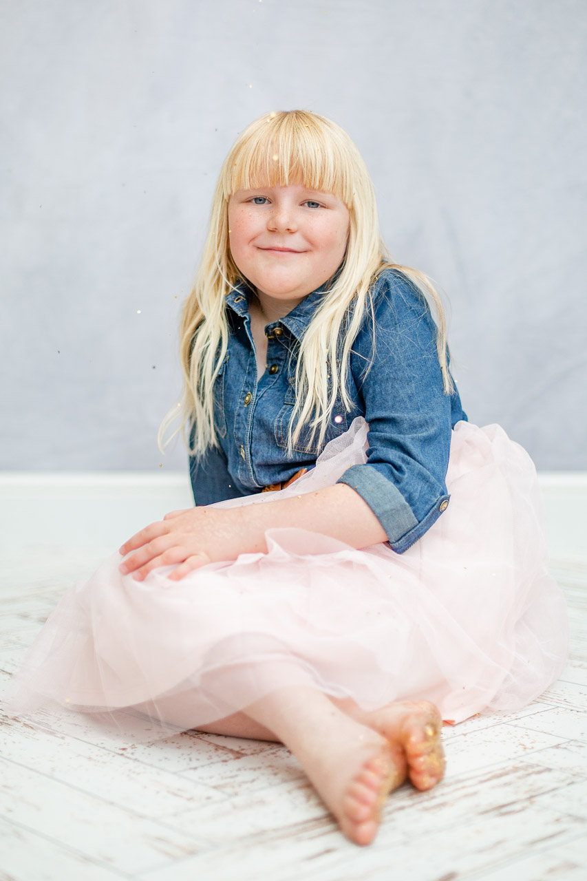 girl wearing tulle and denim dress smiling at camera with glittery feet