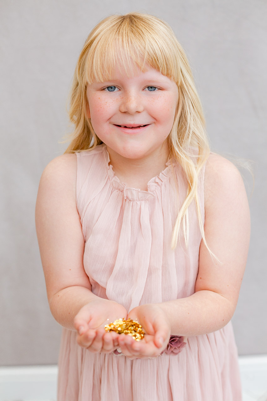 girl cupping gold glitter in hands ready to throw