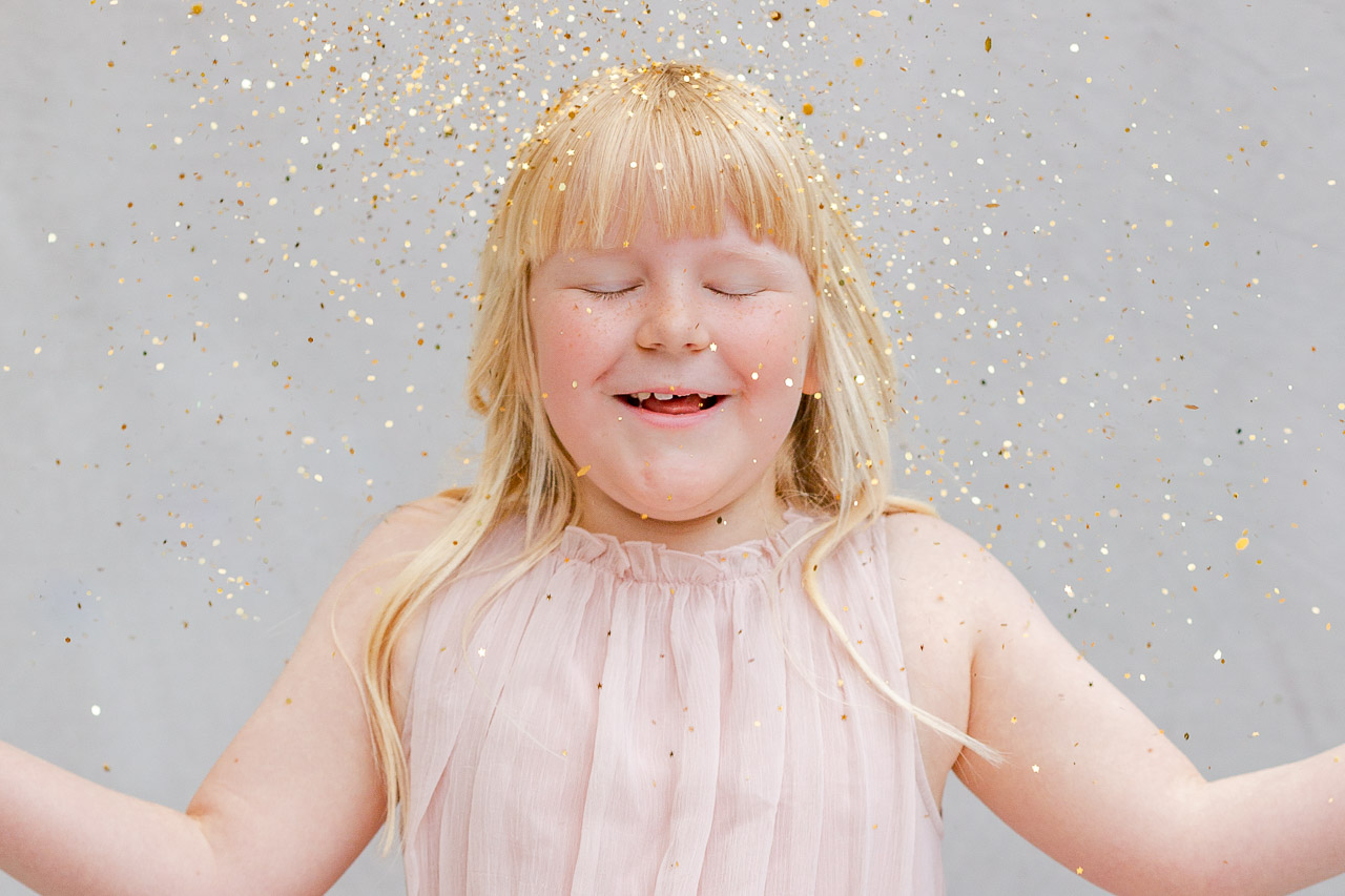 gold glitter falling over little girl in photo studio for glitter photo shoot