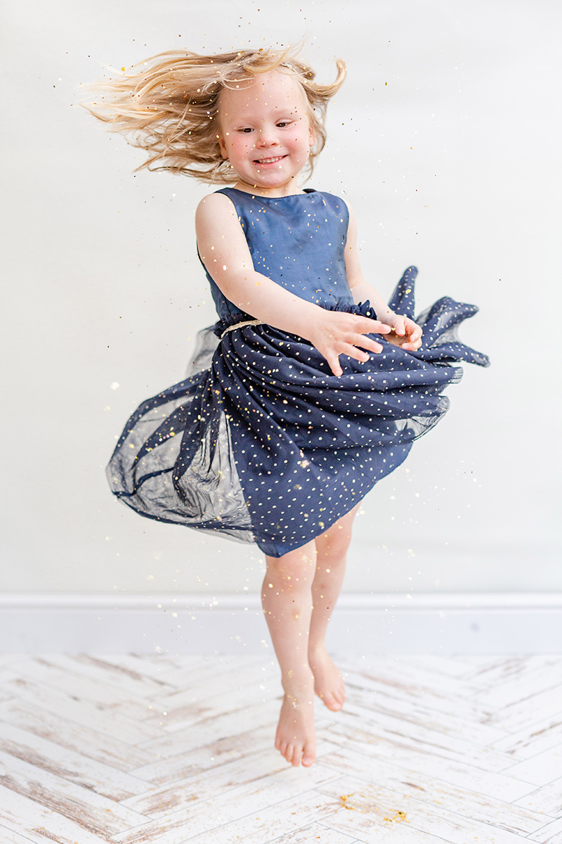 little girl spinning in blue dress glitter photo shoot