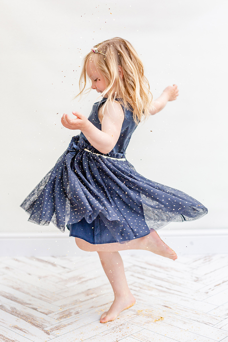 little girl twirling in blue dress for glitter photo shoot