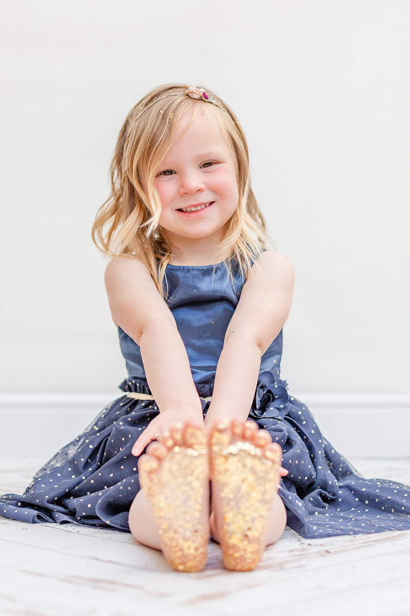 little girl sat on floor in blue dress with glittery feet