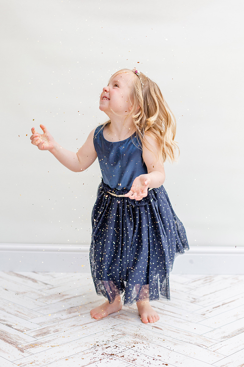 little girl in blue dress looking up at falling glitter for glitter photo shoot