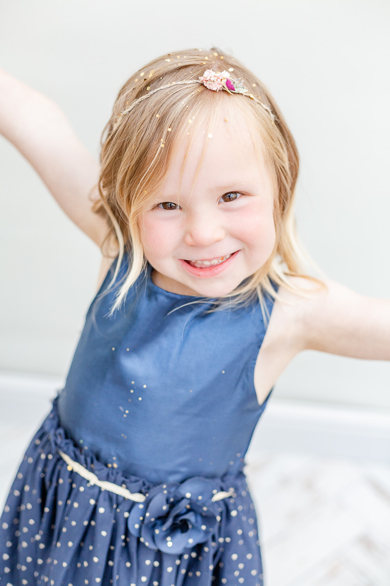 girl with arms wide open smiling at camera with glitter in her hair
