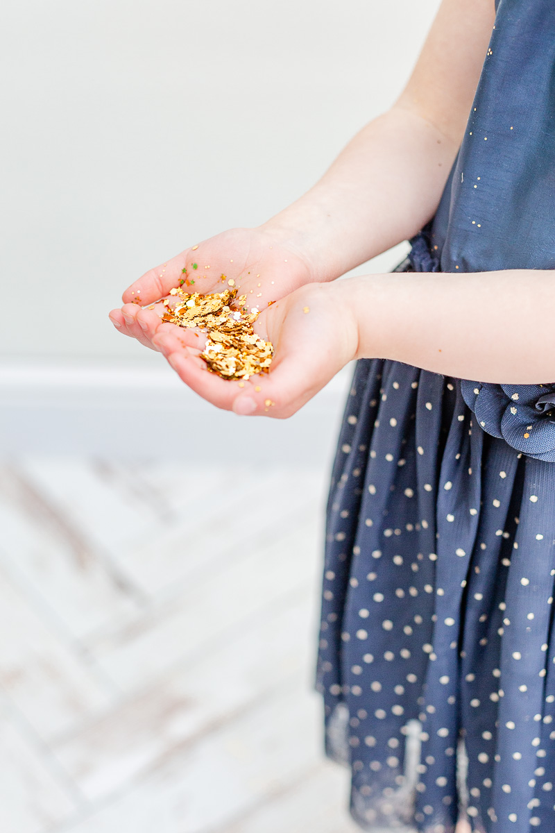 little girls hand full of gold glitter