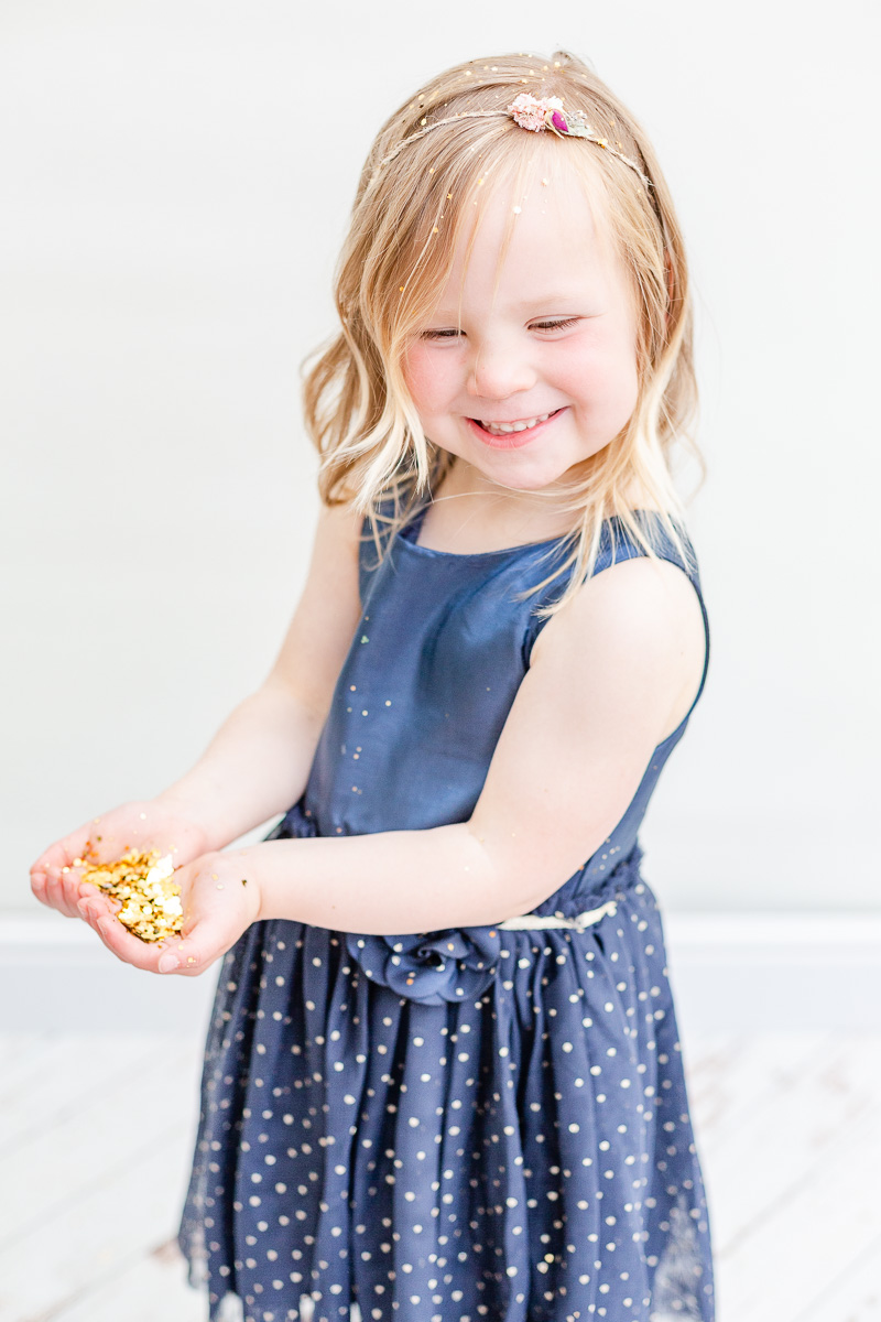 little girl smiling cupping gold glitter