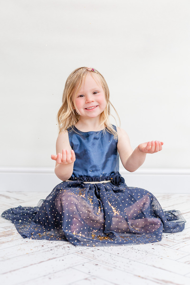 little girl sat on floor with blue tulle dress with glitter falling on her
