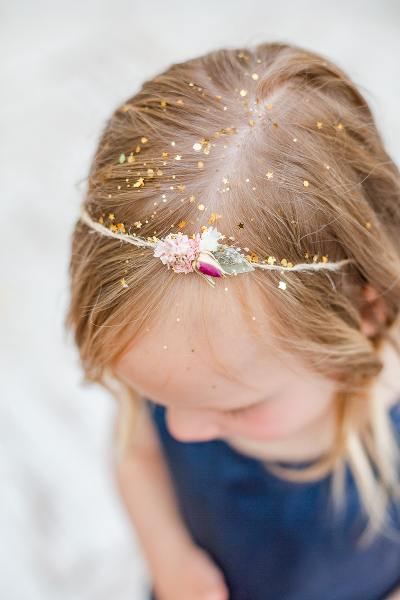 top of little girls head with flower head band and hair covered in glitter