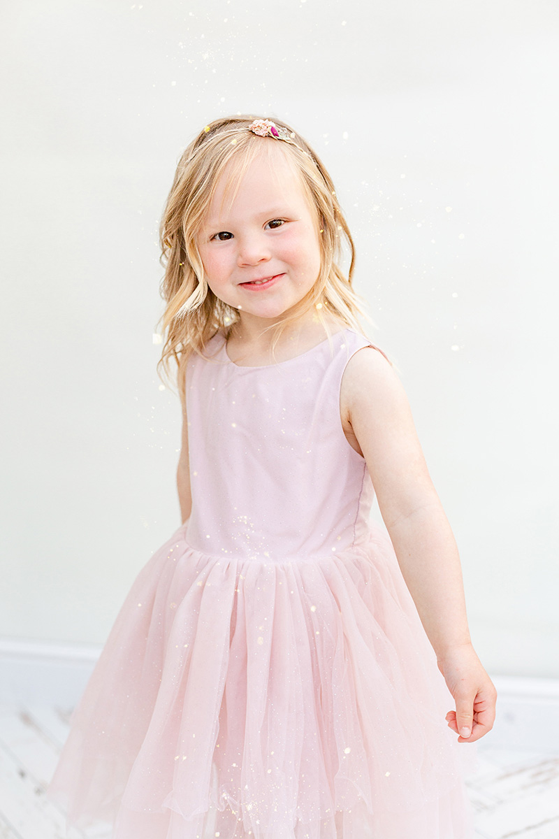 portrait of little girl in pink dress smiling at camera for glitter photo shoot