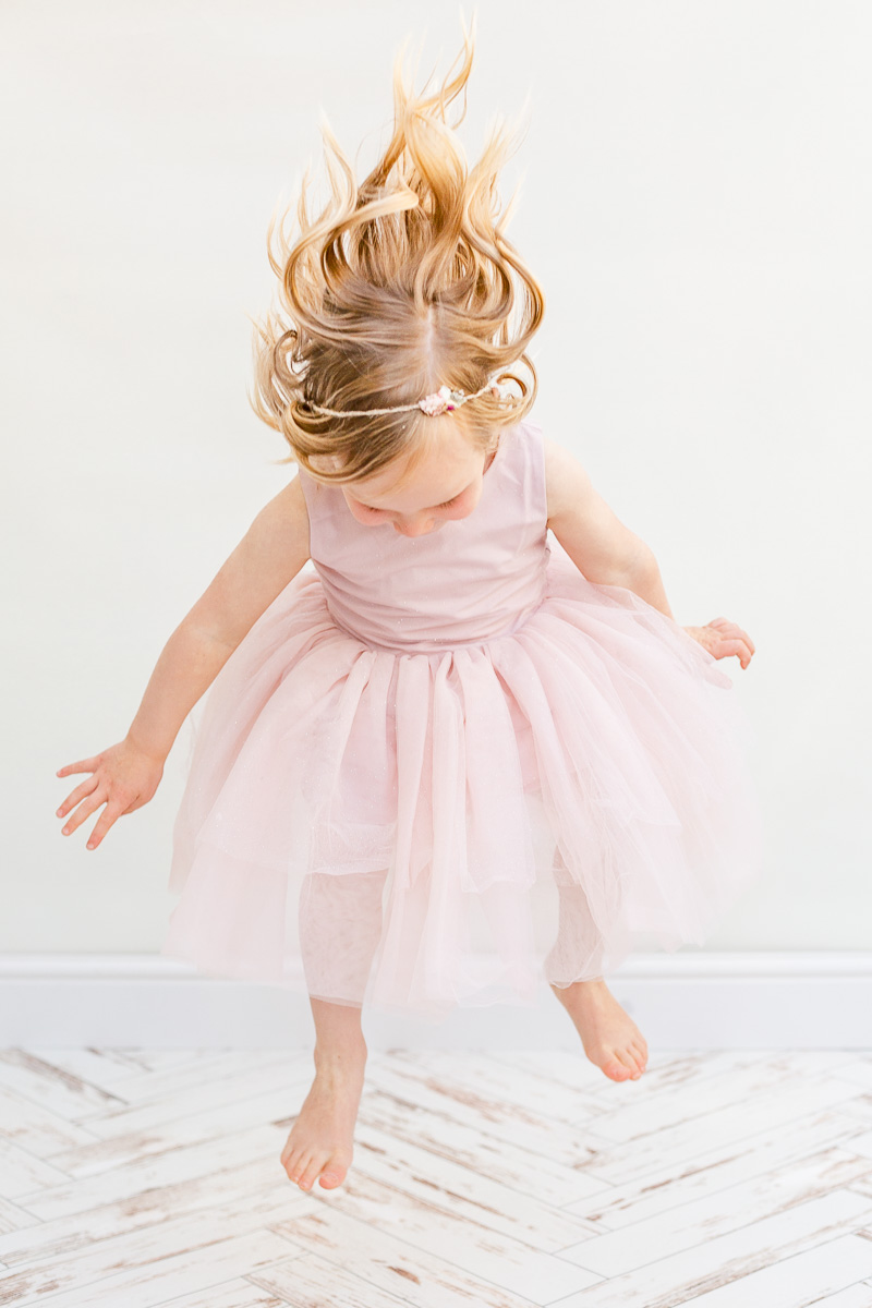 little girl in pink tulle dress jumping up and down