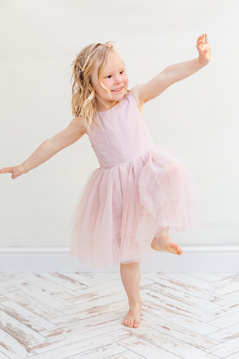 little girl in pink tulle dress dancing in photo studio