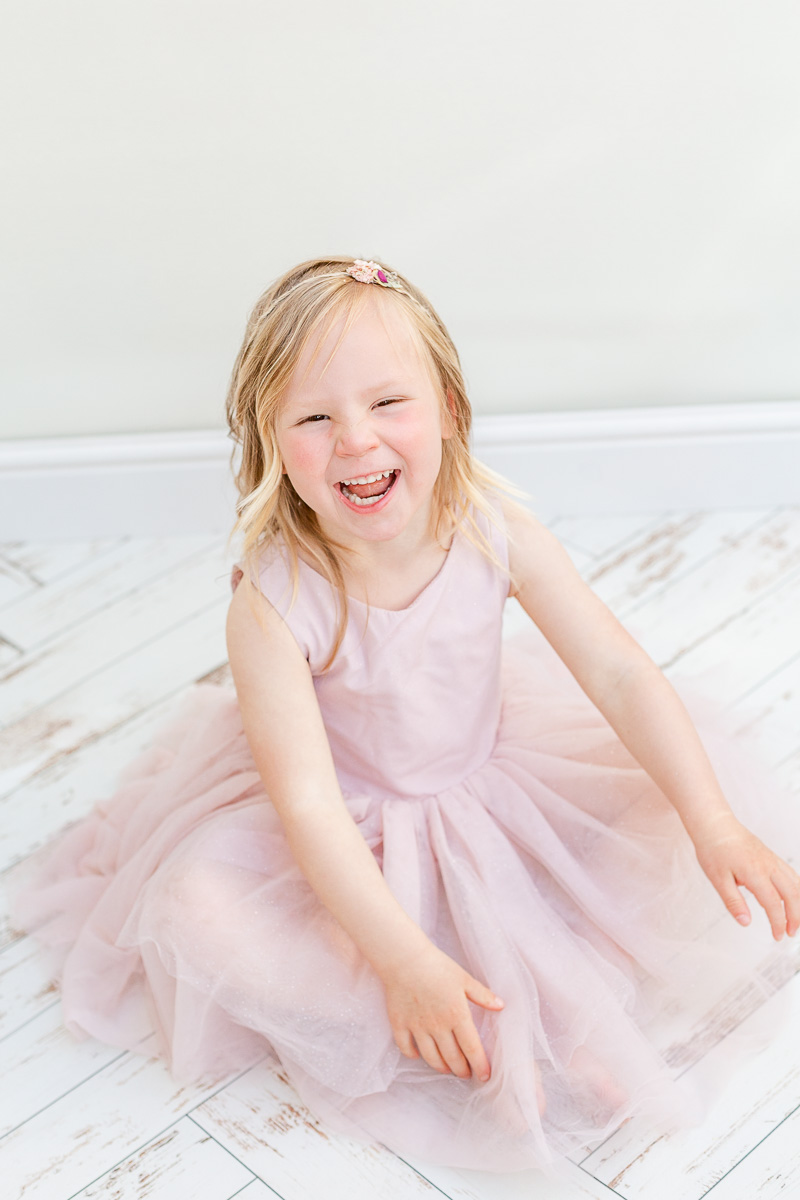 little girl sat on studio floor laughing at camera in pink tulle dress