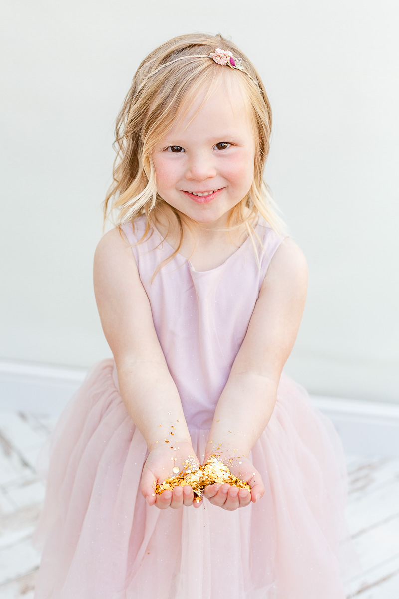 little girl holding handful of glitter ready for glitter photo shoot