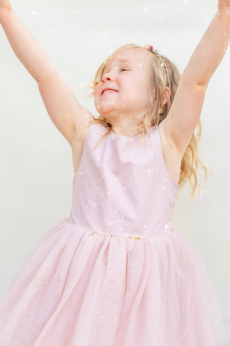 glitter falling onto little girl with arms up