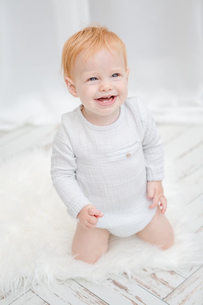 little girl kneeling up smiling at camera