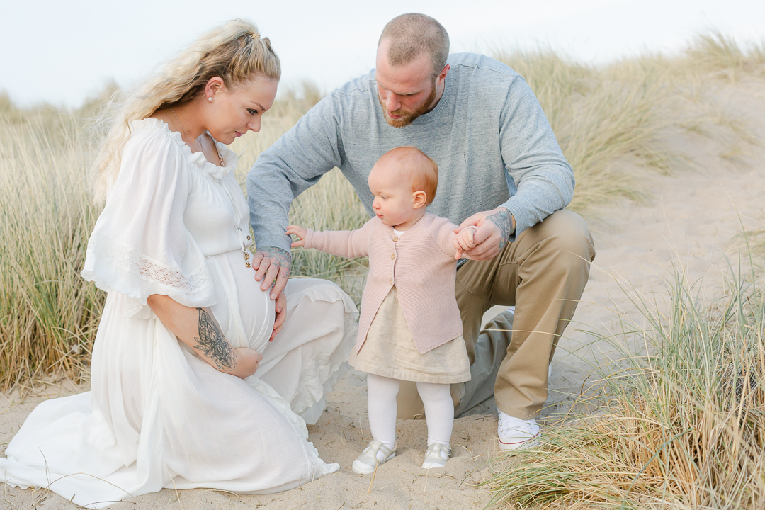 family kneeling in sand dunes toddler and daddy touching mummy's pregnancy bump